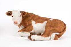 Mooie rustende bruine  koe tuinbeeld kopen